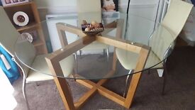 Glass top dining table with wooden frame legs