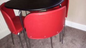 Space saving black table with four red chairs