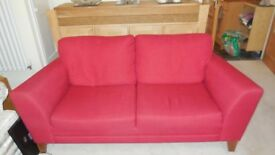 Red fabric two-seater sofa, with beechwood feet, with fire resistant tag