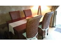 DARK OAK DINING TABLE & FOUR WICKER CHAIRS WITH CREAM CUSHIONS.