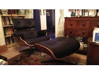 Eames style chair and footstool, as new condition. Black leather and walnut trim. Very comfortable.