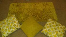 Mustard color rug and cushions.