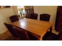Modern solid oak dining room table and 6 matching brown leather chairs