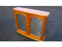 Solid pine bathroom cabinet with mirrored doors in good condition