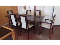Six grey cushioned dining chairs with extending table