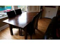 Solid wood Mahogany dining table with extension panal & 4 dark brown leather chairs.