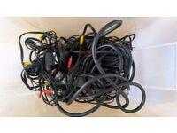 Box of assorted analogue video and audio cables including a long professional SCART cable