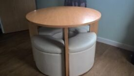 Oak coloured round table and four storage stools