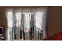 White net curtains with swags and tail