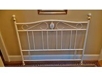 Double divan bed with Victorian style white metal headboard.