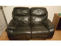 Black leather sofa with footrest