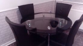 Glass dining table with undershelf and 4 black dining chairs.