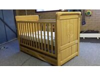 Wooden cot bed with mattress. Excellent condition, includes drawer and bear design etched design.
