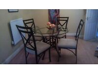 roud glass top dining table with four chair
