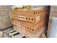 Blackwood. Pallet of new building bricks around 320. Textured red buff garden wall.