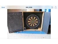 Dart board in wooden cabinet