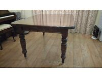 This is a Victorian solid wood wind out table with one leaf and brass casters. seats 4 to 6