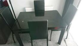 Harvey's black glass and close dinning room table and chairs