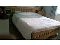 superking wooden bedframe with mattress and bedding