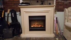 A beautiful fireplace surround. With electric fire. With fake logs behind glass.