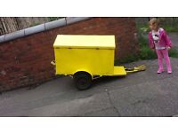 Yellow trailer with hinged lid in shape of a house