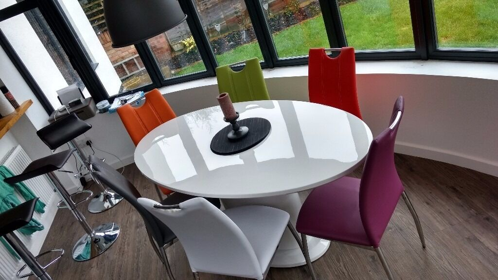 White high gloss table and  multi colour chairs  in Whitstable