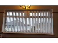 two sets of white vertical blinds and rails
