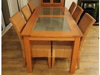 Solid wood and glass dining table with 6 wicker chairs.