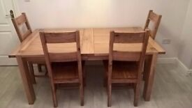 Large oak extending table with 4 chairs and a bench