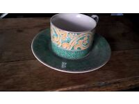 green and cream tea cup and saucer