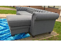 A New Hampton 3 Seater Grey Fabric Material Buttoned Back L-Shaped Lounger.
