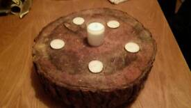 Sliced wooden logs with tea lights and votive candle