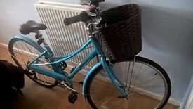 Blue vintage esque bike with basket and accessories.