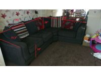 Large black corner sofa with striped and floral cushions.