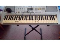 Yamaha psr 290 keyboard with some music in used but working condition with stand and adaptor