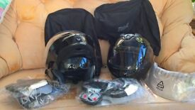 Two black flip face motorbike helmets with slide down sun visor