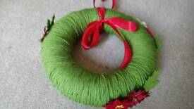 Wool polystyrene wreath and poinsettia flowers on it and ribbon