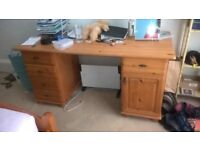 large pine desk with drawers.