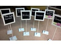 Wedding table name signs and large glass tea light holders.