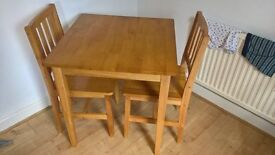 lovely rubberwood table and 2 chairs, H75cmXW70cmXL70cm, see photos for condition.