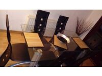 Glass dining table including six black chairs