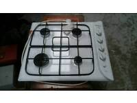 Un used Indesit 4 ring gas hob with electric ignition in white.