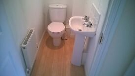 A white cloakroom toilet with close couple cistern, seat and lid.