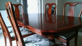 Hardwood dining room table and 6 chairs (2 with arms, 4 without) with an additional section / leaf.