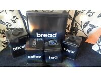 5 piece black canister set along with mug rack and kitchen towel holder