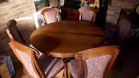 Extending round dark oak dinning table and six matching wood and upholstered chairs