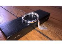 Silver coloured bracelet with dropper tassle