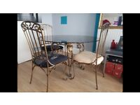 Iron table with solid glass top and four chairs