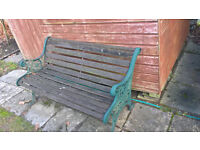 Wooden garden bench with green ironwork sides
