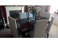 Dark wood dining table and 6 white covered chairs